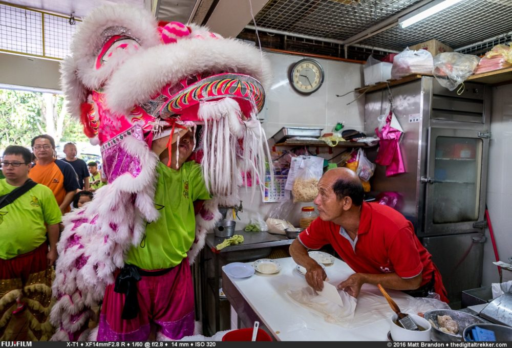 Albert, the Chee Cheong Fun hawker, sneaks a peak at the man behind the lion mask.
